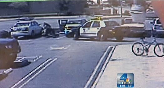 A screenshot from NBCLA shows an arrest in a parking lot in which an officer wrestles a driver to the ground.