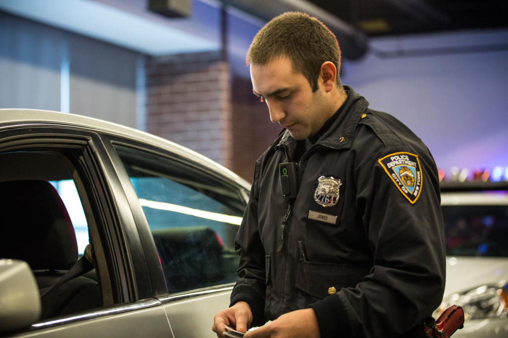New York Police Department (NYPD) Officer Joshua Jones wears a body camera during a mock traffic stop to demonstrate how the cameras will be used during a press conference.