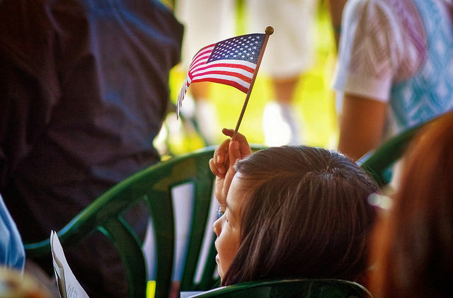 A girl waves the flag at a naturalization ceremony, July 2010