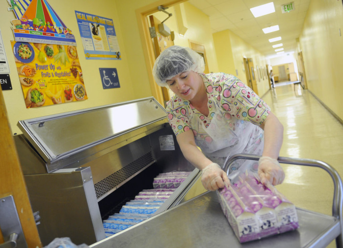 Cafeteria worker Sophia Villareal fills a cooler with milk before the lunch period at Brockton Avenue Elementary School in Los Angeles. A 2012 federal report found the most popular a la carte items sold are chips, followed by cookies, pizza and milk.