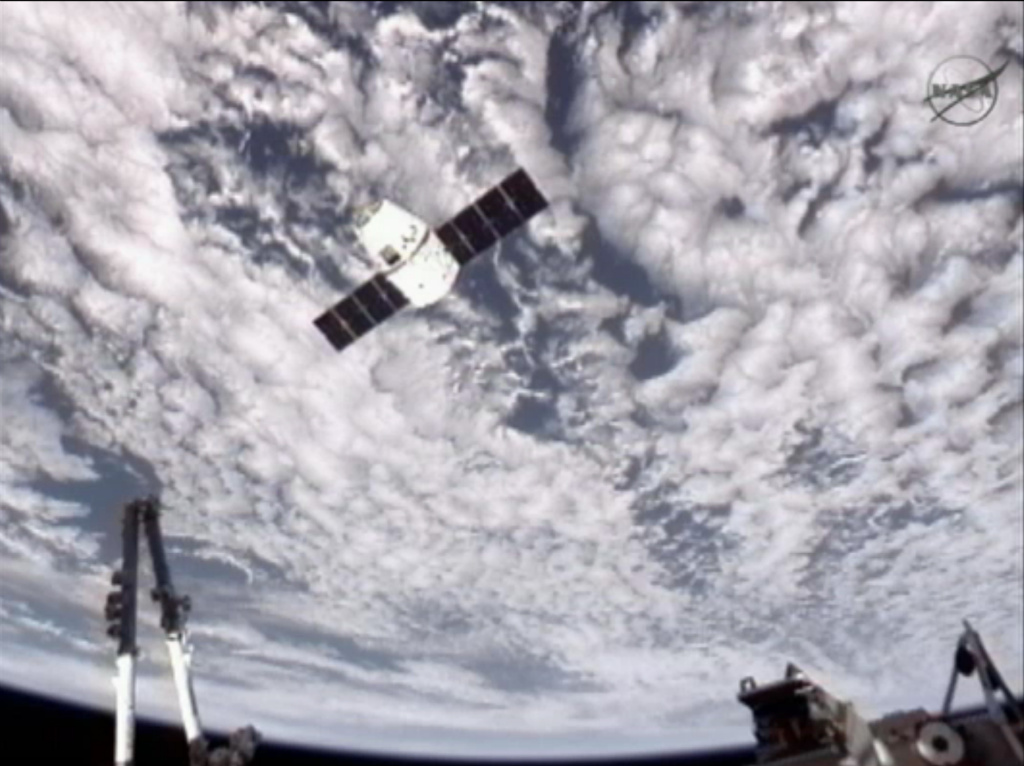 This image provided by NASA-TV shows the SpaceX Dragon commercial cargo craft, top, as Dragon approaches the International Space Station, Friday, May 25, 2012. Dragon is scheduled to spend about a week docked with the station before returning to Earth on May 31 for retrieval.