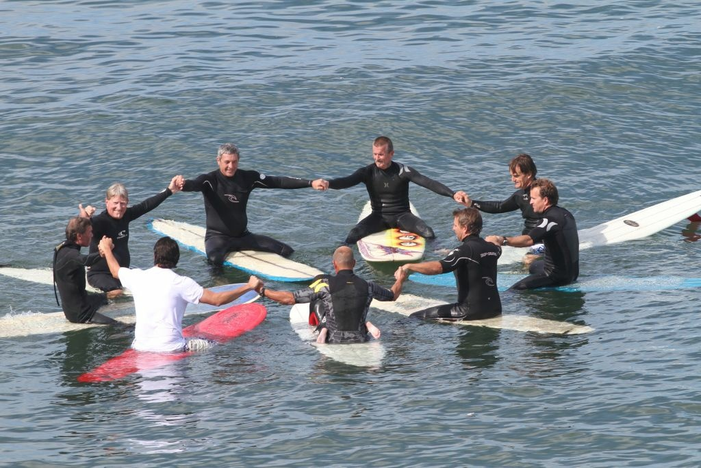 Surfers hold hands at last year's