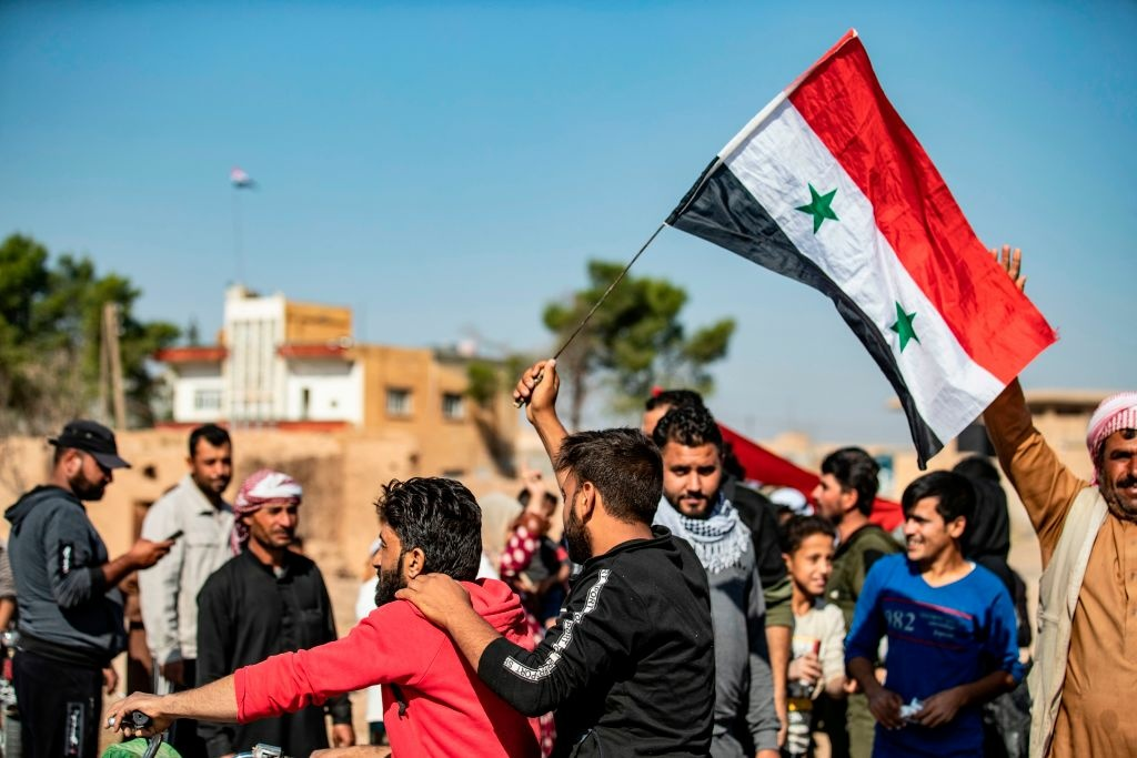 Locals welcome Syrian regime forces as they arrive at the western entrance of the town of Tal Tamr in the countryside of Syria's northeastern Hasakeh province on October 14, 2019