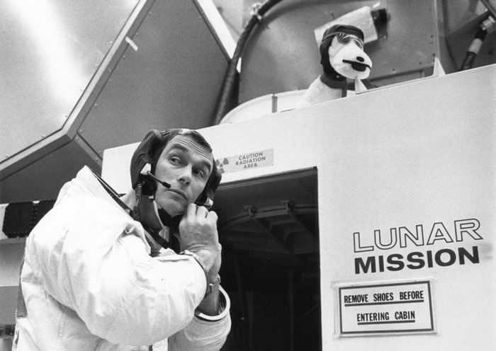 Gene Cernan prepares for his 1969 Apollo 10 flight, adjusting his headset outside a lunar module simulator.