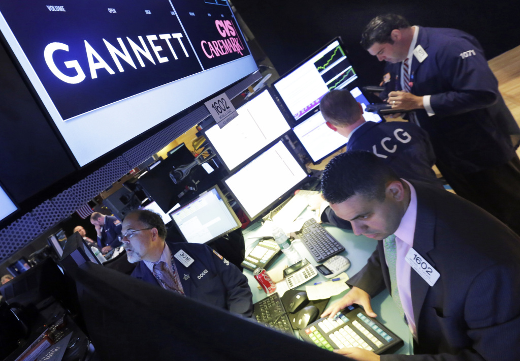 Specialist Michael Cacace, foreground right, works at the post that handle Gannett, on the floor of the New York Stock Exchange, Tuesday, Aug. 5, 2014. Gannett is splitting its broadcast and publishing business in two, joining other major media players in allowing fast growing TV and digital operations to operate more freely and not be weighed down by the declining newspaper business.