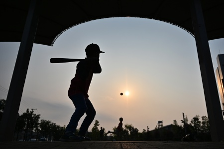 Boys play a game of baseball in Kosuge in Tokyo on April 22, 2019.