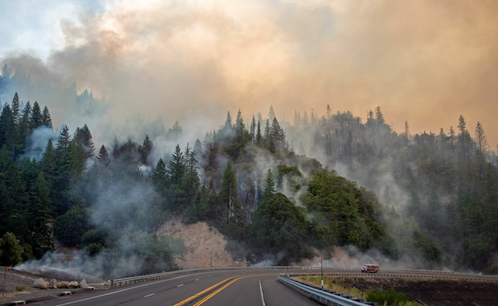 TOPSHOT - A fire truck drives along Highway 299 as they Carr fire continues to burn near Whiskeytown, California on July 28, 2018. - The US federal government approved aid on July 28 for California as thousands of firefighters battled to contain a series of deadly raging wildfires that have killed six people, including two young children and their great grandmother, and destroyed hundreds of buildings. (Photo by JOSH EDELSON / AFP)        (Photo credit should read JOSH EDELSON/AFP/Getty Images)