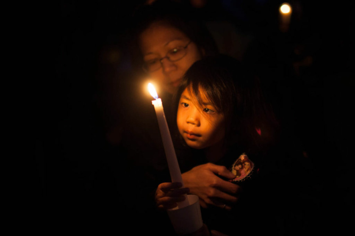 Jesslyn Fukushima, 3, holds a candle at a vigil on December 15 at Glenoaks Park in Glendale for the victims of a mass shooting at Sandy Hook Elementary School in Newtown, Conn.