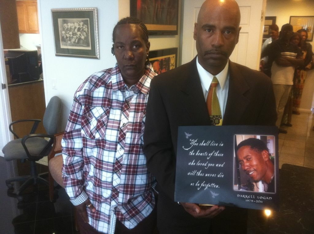Arzenia Ratlyff and Darrell Logan hold a photo of their son Darrell Logan, Jr.