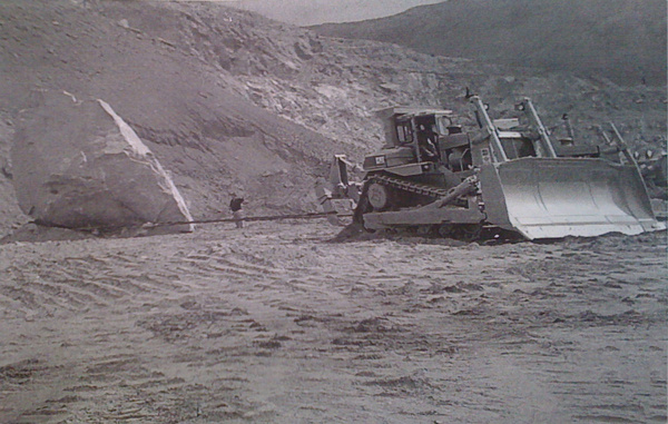 Early image of artist Michael Heizer (4th from left) and quarry crew, with the 340-ton rock that will form part of Heizer's sculpture,