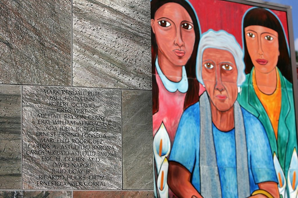 Figures on a mural stand near names of AIDS victims on a granite panel of The Wall - Las Memorias AIDS monument November 28, 2006 in Los Angeles, California.