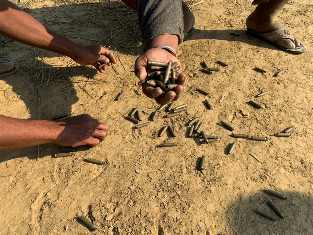 This photo taken on January 28 shows residents holding bullet shells in a village in Rathedaung township, Rakhine state, where fighting between the Myanmar military and ethnic Arakan Army took place from January 26 to 28. Amnesty International estimates the violent clashes, which are ongoing, have displaced about 30,000 since January.