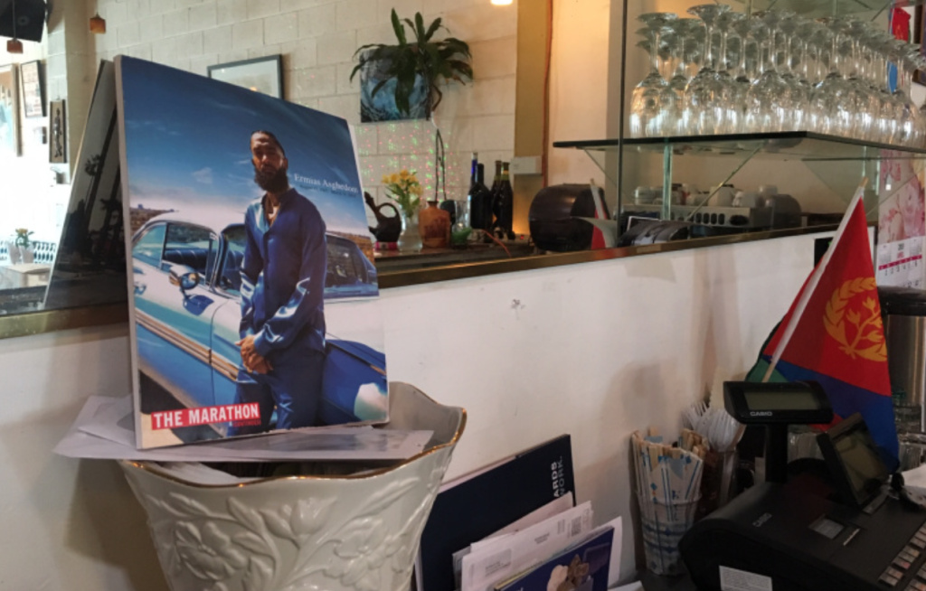 A photo of Nipsey Hussle from his recent memorial service sits behind the bar at Industry Cafe & Jazz in Culver City. Its owner, Aron Tadesse, is part of the same tightly knit local Eritrean community that Hussle, the son of an Eritrean immigrant father, was raised in.