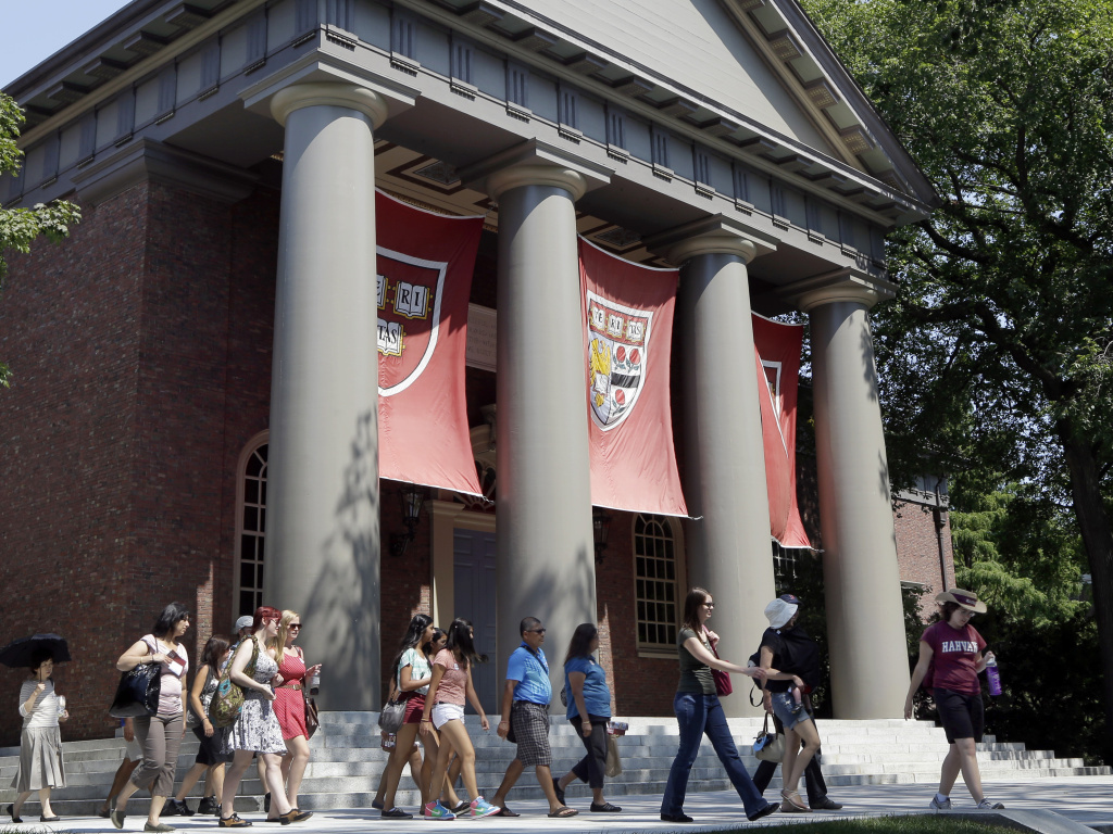 People are led on a tour of the campus of Harvard University in Cambridge, Mass, in 2012. Harvard was one of 27 institutions on the Education Department's newly released list.