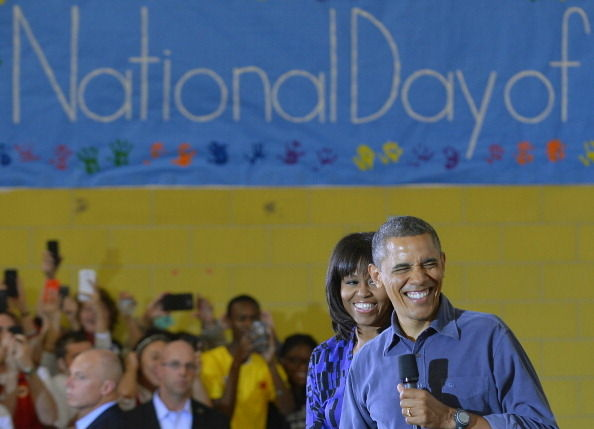 US President Barack Obama (R) and First Lady Michelle Obama greet a crowd at Burrville Elementary School after participating in National Day of Service on January 19, 2013 in Washington DC, as part of the 57th Presidential Inauguration.