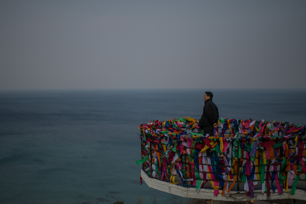 A man stands on a viewing platform covered with ribbons bearing goodwill messages as he looks towards North Korea from Goseong Unification Observatory on February 22, 2018 in Goseong-gun, South Korea.