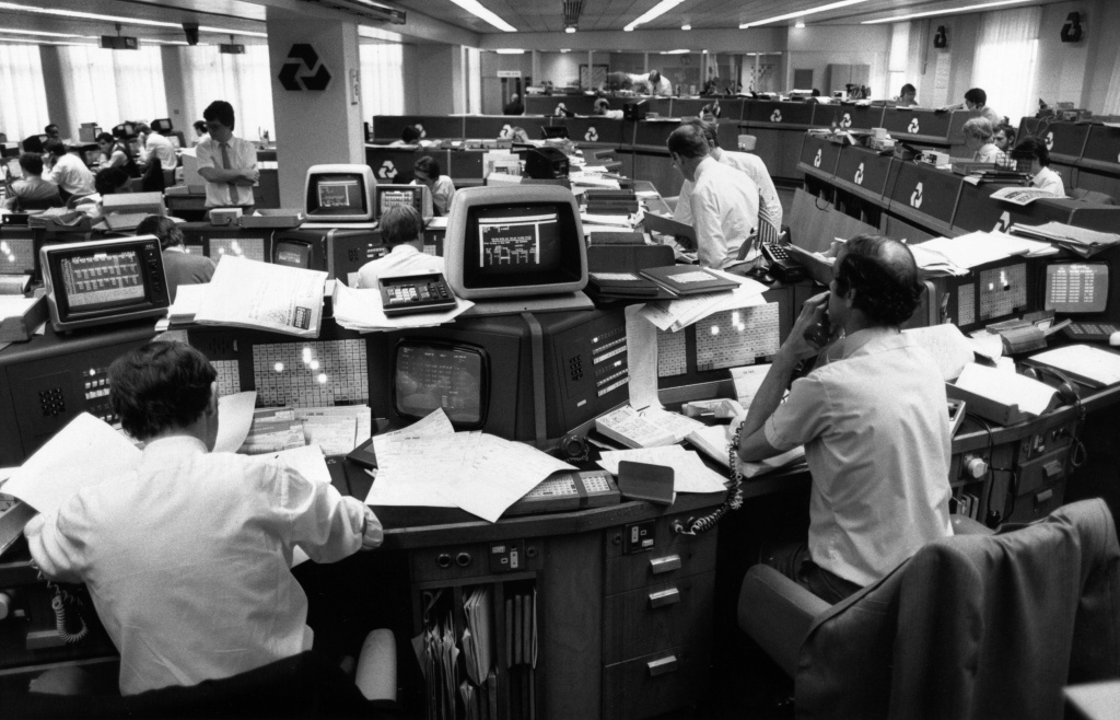 People at work on computers in an office at a National Westminster bank, circa 1990.