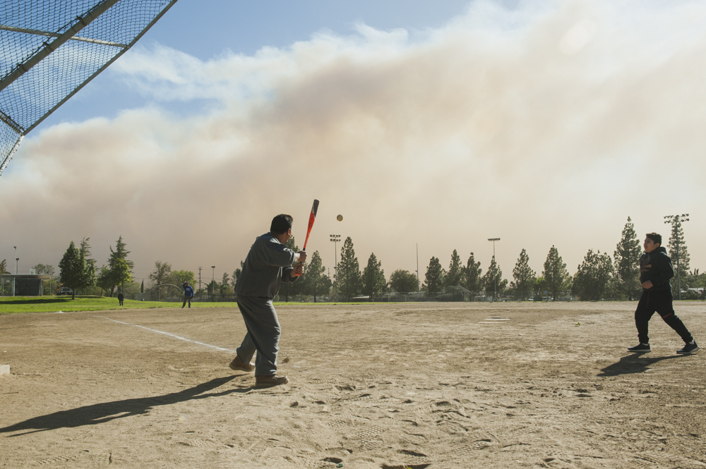 Alan Gonzalez hits a baseball to relatives in the field outside the Sylmar Recreation Center, where their family evacuated to this morning, as smoke from the Creek Fire billows in the background in Sylmar on Dec. 5, 2017.