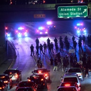 Police and protesters face off on a freeway in downtown Los Angeles, California after midnight early on November 10, 2016 as protesters angry over Donald J. Trump's election as the next US president marched in downtown Los Angeles through the evening and shut down portions of the Hollywood (101) Freeway. Thousands of protesters rallied across the United States expressing shock and anger over Donald Trump's election, vowing to oppose divisive views they say helped the Republican billionaire win the presidency. / AFP / Frederic J. BROWN        (Photo credit should read FREDERIC J. BROWN/AFP/Getty Images)
