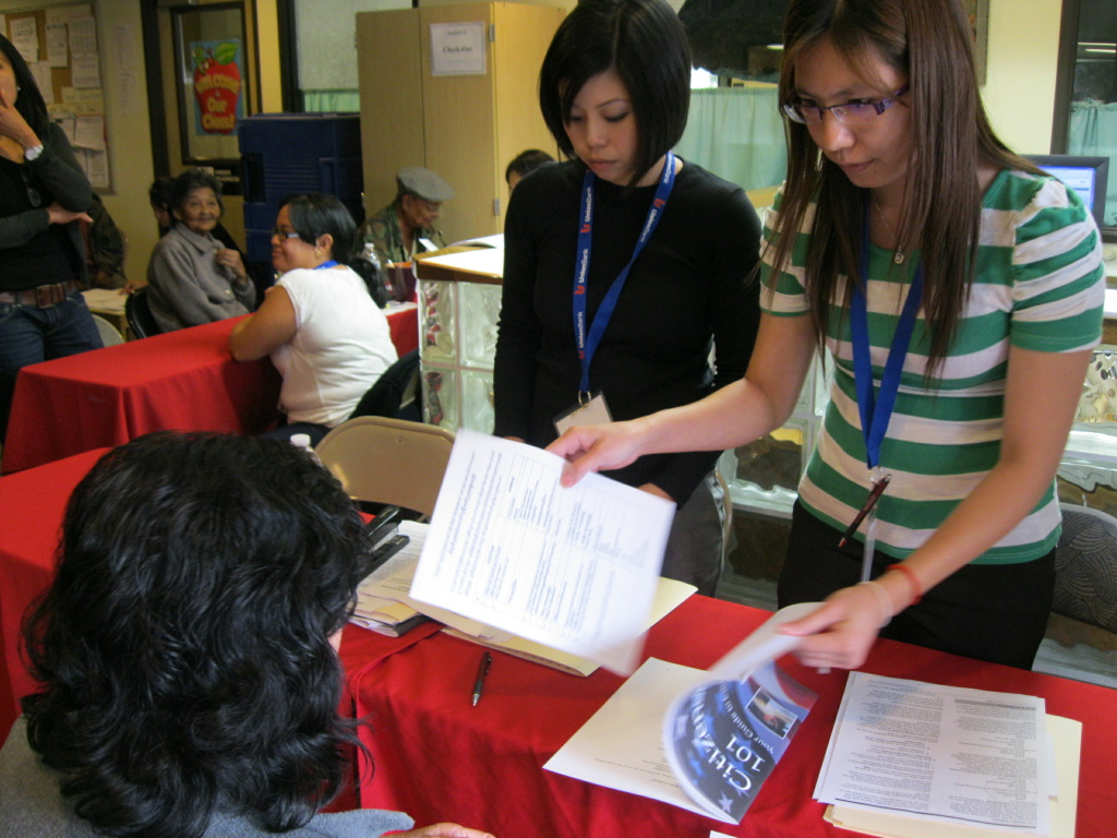 Volunteer attorney Pancy Lin Misa and Sokly Prom, a volunteer for The Cambodian Family, help a prospective new U.S. citizen fill out naturalization paperwork at a June 2011 citizenship drive in Santa Ana.