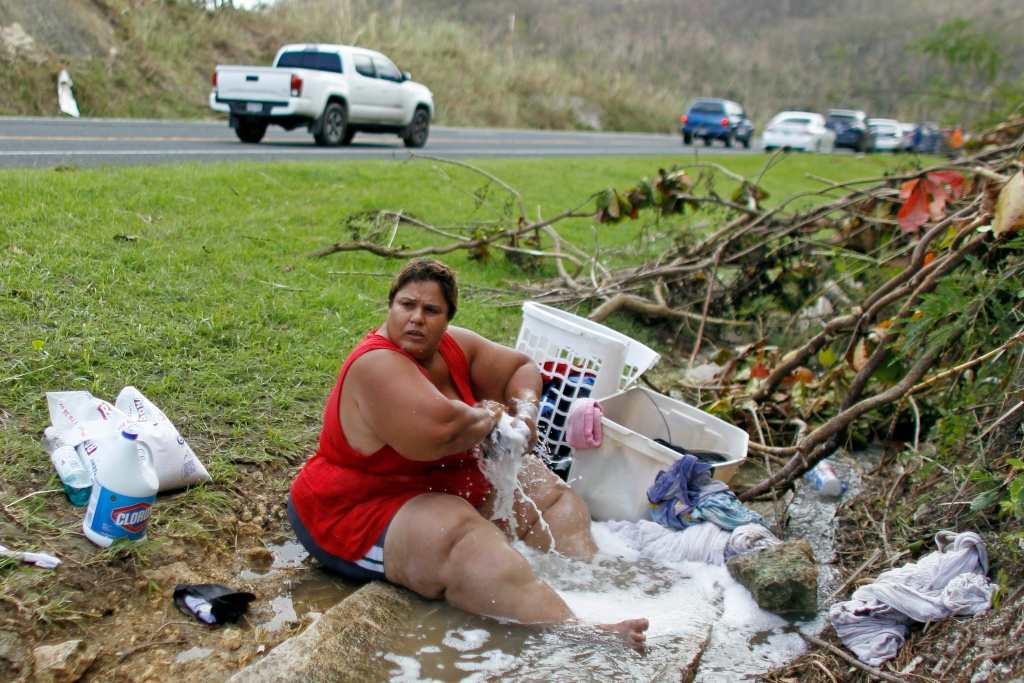Iris Vazquez washes clothing at a drainage ditch next to a road in Corozal, west of San Juan, Puerto Rico, on September 24, 2017 following the passage of Hurricane Maria.