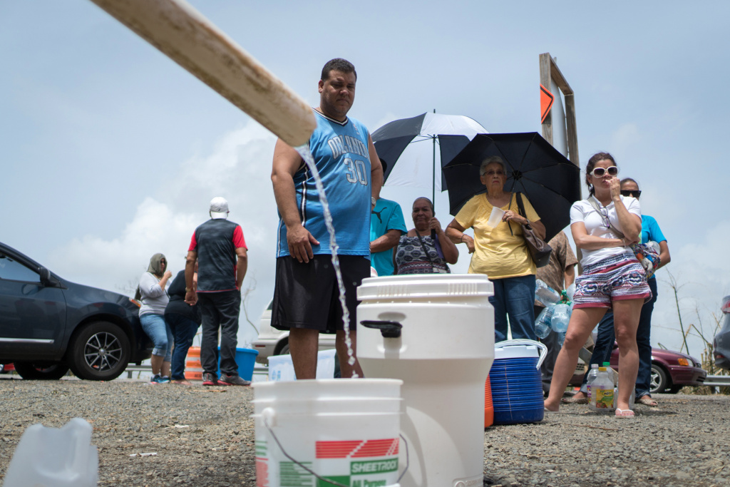 People fill containers with water from a stream near the PR52 expressway in Cayey, Puerto Rico, on Tuesday. People have been without water service in their homes after Hurricane Maria roared through a week ago.