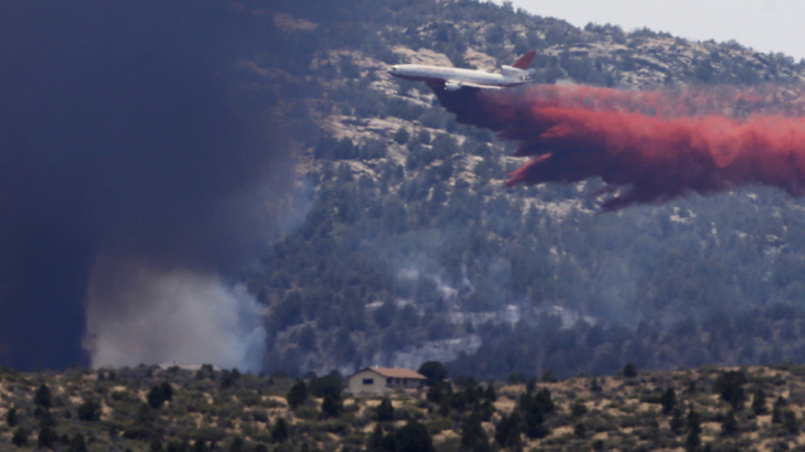 An aerial tanker drops fire retardant on a wildfire threatening homes near Yarnell, Ariz., on July 1. An elite crew of firefighters was overtaken by the out-of-control blaze on June 30, killing 19 members as they tried to protect themselves from the flame