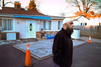 A worshipper who asked not to be identified walks away from the locked Islamic Circle of North America mosque in Alexandria, Va,, Thursday Dec. 10, 2009. The mosque is linked to the five Americans detained in Pakistan and is next door to the home of the detained Umar Farooq.