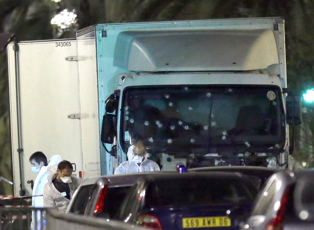 Forensic officers stands near a truck with its windscreen riddled with bullets, that plowed through a crowd of revelers who'd gathered to watch the fireworks in the French resort city of Nice, southern France, Friday, July 15, 2016. At least 80 people were killed before police killed the driver, authorities said. (AP Photo/Claude Paris)