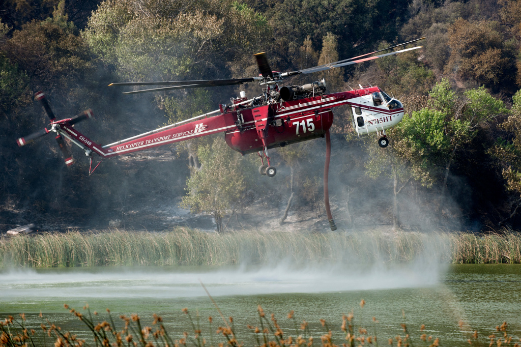 Fire officials said Monday that 12 helicopters and 967 firefighters are battling the 3,800 acre Hathaway Fire in Riverside County in heavy chaparral and timber.  (File photo: Helicopters pick up water from Lake Hughes to put out flames at the Powerhouse Fire in northwest L.A. County in May).