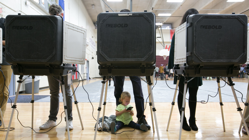 A 2-year-old waits between her father's legs as he and other voters cast their ballots at a polling station set up at Grady High School in Atlanta on Election Day. The state is one of a handful that still use voting machines that don't provide a paper record.