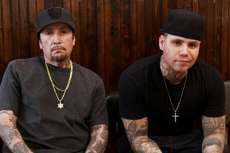 Freddy Negrete (left) at the Shamrock Social Club where he tattoos alongside his son, Isaiah.