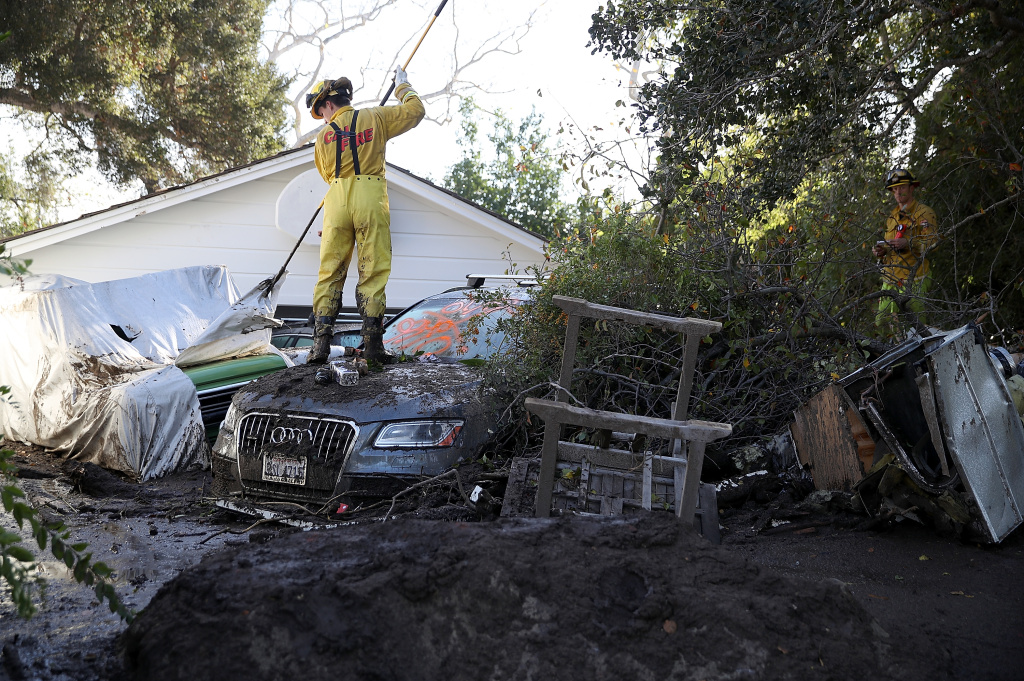 A Cal Fire firefighter looks through a car next to a home that was destroyed by a mudslide on January 12, 2018 in Montecito, California.