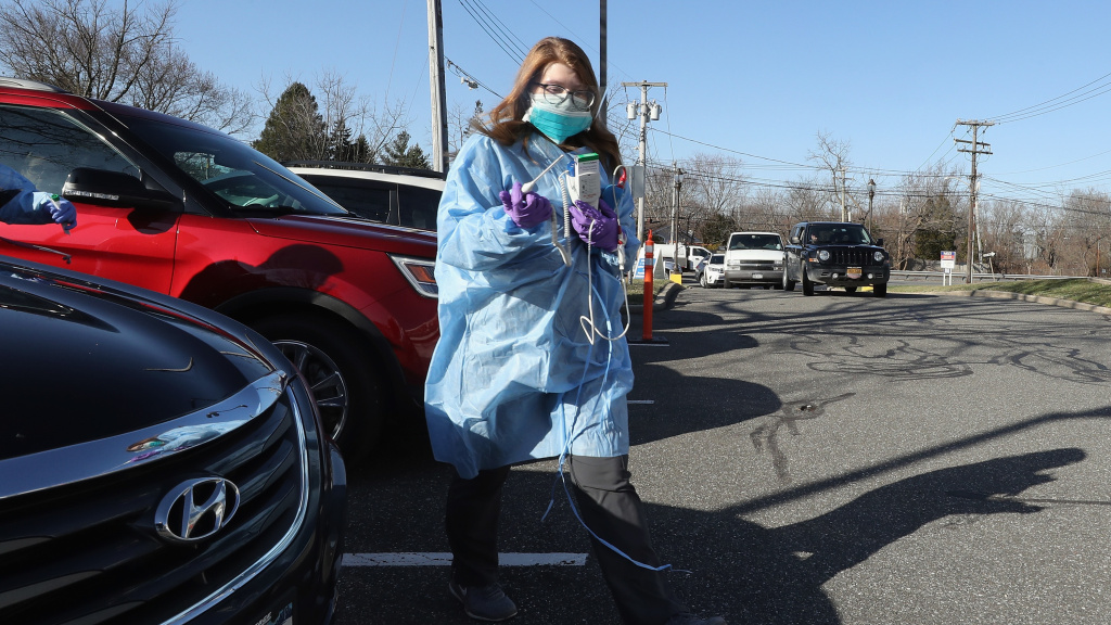 Workers tend to patients at a drive-in center in Jericho, N.Y., that is offering COVID-19 testing.