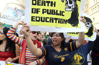Demonstrators carry signs as they march to Oakland City Hall during a national day of action against school funding cuts and tuition increases on March 4, 2010 in Oakland. Students across the country walked out of classes and held demonstrations against massive tuition increases and funding cuts to college universities.