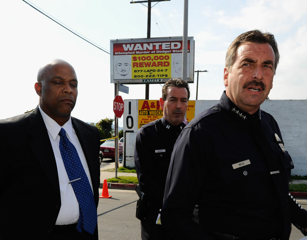 Los Angeles Police Department police chief Charlie Beck (R) standing in front of one of 300 billboard showing a
