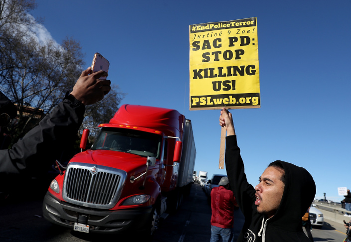 Black Lives Matter protesters hold signs as they stage a demonstration outside of Sacramento City Hall on March 22, 2018 in Sacramento, California. Hundreds of protesters staged a demonstration against the Sacramento police department after two officers shot and killed Stephon Clark, an unarmed black man, in the backyard of his grandmother's house following a foot pursuit on Sunday evening.