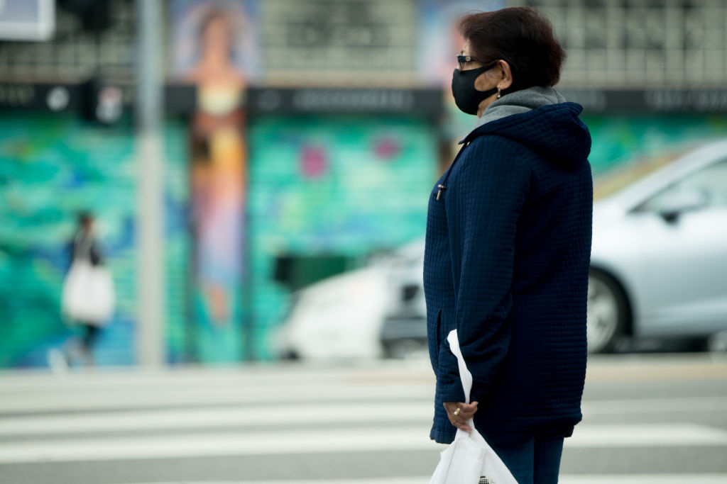 A pedestrian wearing a face mask waits to cross the street during the coronavirus pandemic on April 08, 2020 in Los Angeles, California.