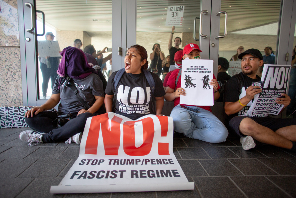 Michelle Xai, center, leads a chant as she and other demonstrators block the doors to the Metropolitan Detention Center to protest migrant family separations stemming from the Trump administration's zero-tolerance policy along the border, in Los Angeles, California, June 21, 2018.