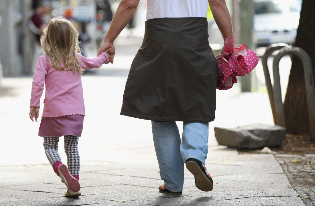 A father and daughter walk in the city center in Berlin, Germany.