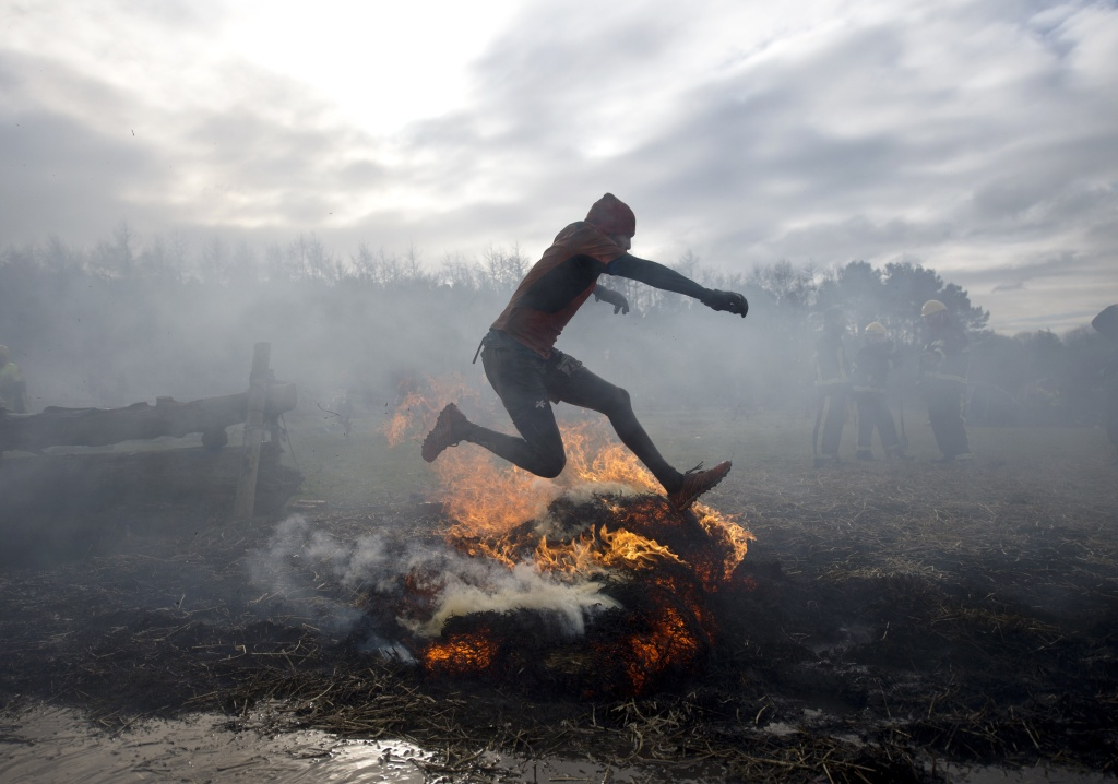 A competitor jumps over fire as he takes part in the