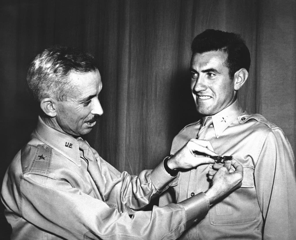 Brig. Gen. Isaiah Davics, commanding general at Midland, Tex., Army Flying School, pins a pair of silver bombardier wings Lieutenant Lou Zamperini on August 14, 1942. In 1936 Zamperini, international track star, while in Berlin for the Olympic Games as Uncle Sam's ace miler, yanked down a Nazi swastika right in front of Hilter's Palace.