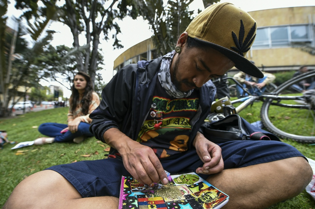 An activist in Bogota, Colombia rolls a joint under the motto