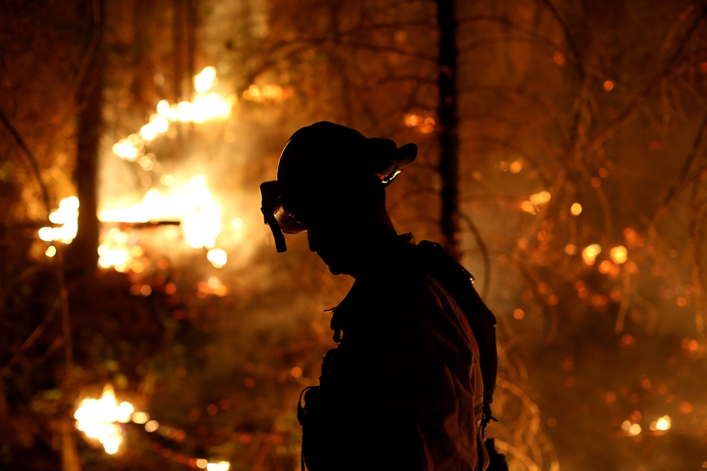 GROVELAND, CA - AUGUST 22:  A firefighter from Cosumnes Fire Department monitors a back fire while battling the Rim Fire on August 22, 2013 in Groveland, California. The Rim Fire continues to burn out of control and threatens 2,500 homes outside of Yosemite National Park. Over 1,000 firefighters are battling the blaze that was reduced to only 2 percent containment after it nearly tripled in size overnight.  (Photo by Justin Sullivan/Getty Images)