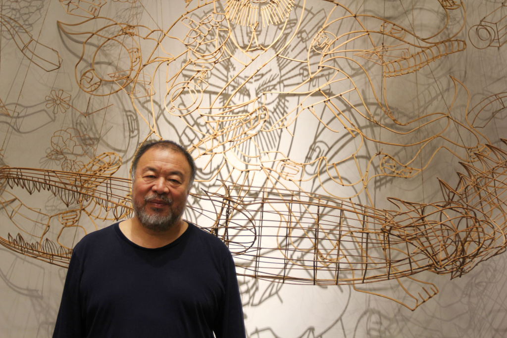 Chinese artist Ai Weiwei stands before a bamboo self-portrait at the Marciano Art Foundation in Los Angeles.