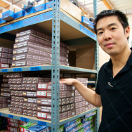AirSplat CEO Kenneth Wu, in front of an aisle of airsoft guns.