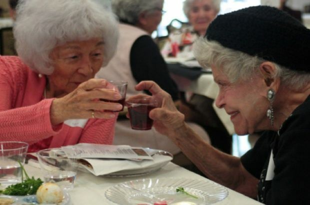 Betty Uchida and Lucille Weiss clink glasses during the Seder ritual in Boyle Heights, April 2, 2012