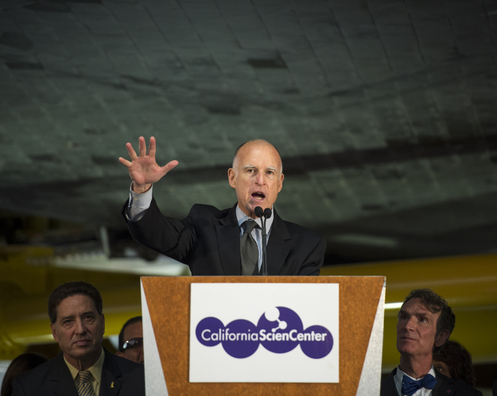 California Governor Jerry Brown speaks from a podium underneath the space shuttle Endeavour during the grand opening ceremony for the California Science center's Samuel Oschin Space Shuttle Endeavour Display Pavilion, on October 30, 2012, in Los Angeles, California.