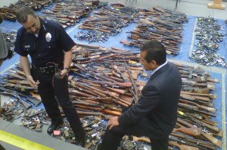 Los Angeles Police Chief Charlie Beck and Mayor Antonio Villaraigosa stand over the more than 2,500 guns recovered through the city's gun buyback program.