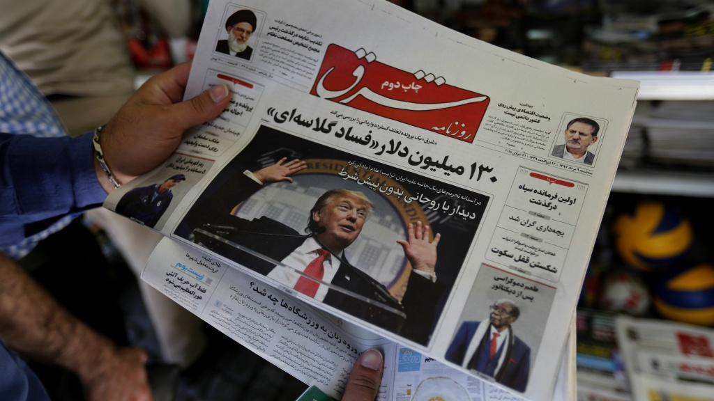 A man in Tehran looks at a newspaper with a picture of President Trump on the front page on Tuesday. Iran's currency traded at a fresh record-low of 119,000 to the dollar today, a loss of nearly two-thirds of its value since the start of the year as U.S. sanctions loom. Trump says he's willing to meet with Iranian leaders, but Iran doesn't seem eager to sit down.